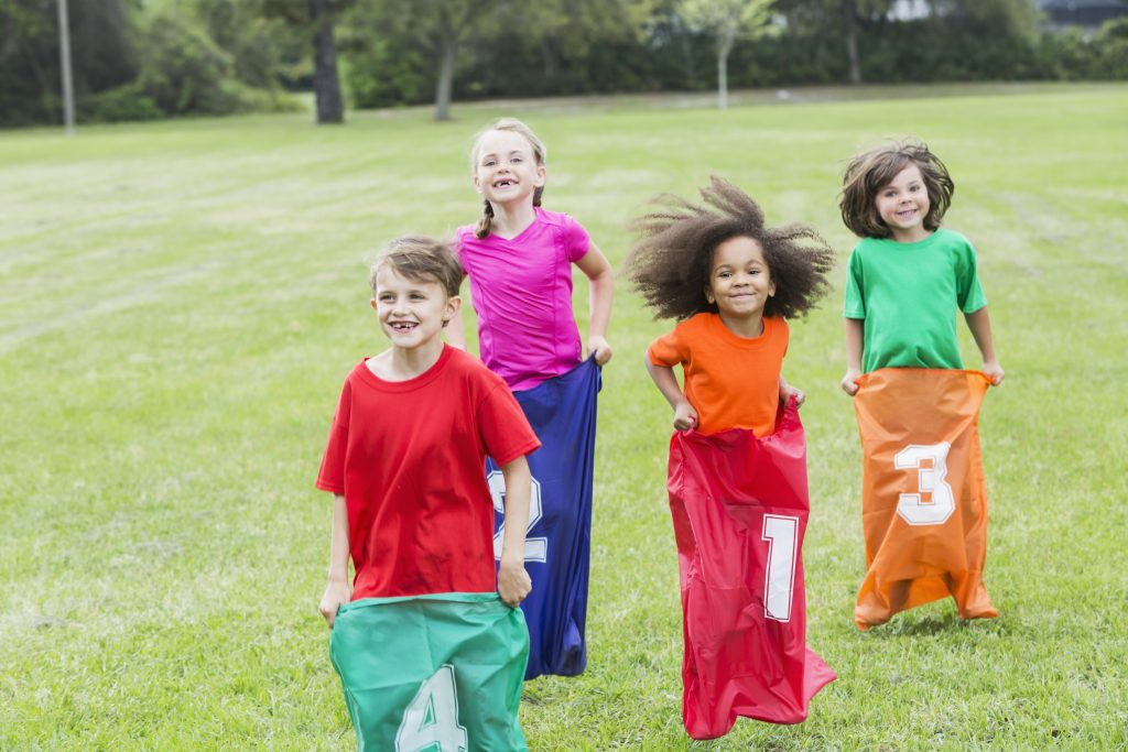 Four multiracial children in potato sack race